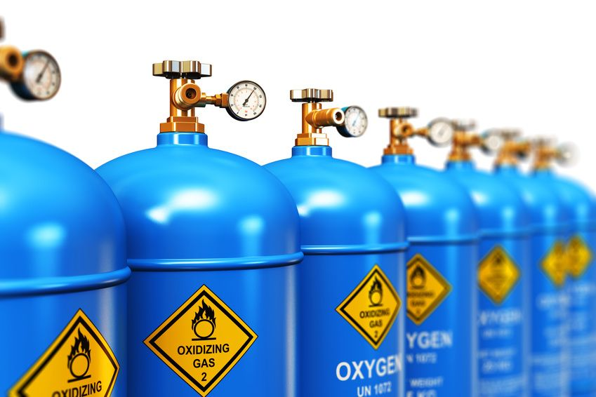 Creative abstract fuel industry manufacturing business concept: 3D render illustration of the group of blue metal steel liquefied compressed natural oxygen gas containers or cylinders for welding or medical use with high pressure gauge meters and valves arranged in row and isolated on white background with selective focus effect